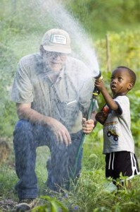 Community gardener John Doran has help from Zorte Edo, 3, watering a patch of vegetables. Zorte's father Keniabarido also gardens at the Antelope Community Garden.(William Lauer)